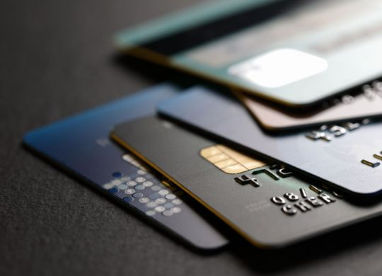 stack of multicolored credit cards on black background
